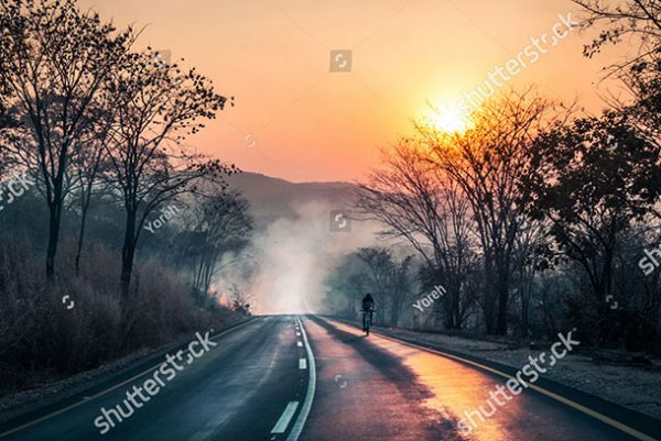 stock-photo-cyclist-passing-fire-and-smoke-with-the-sun-reflecting-on-tarmac-during-sunset-on-mountainbike-696776392