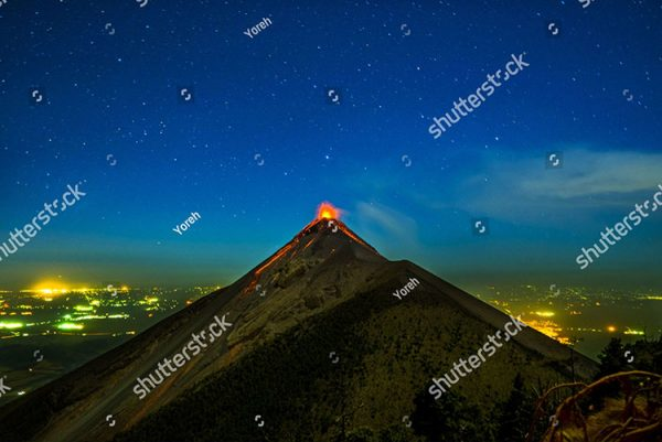 stock-photo-fuego-volcano-erupting-with-lava-at-night-with-stars-and-town-in-background-in-guatamala-1015868107