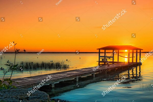 stock-photo-sunrise-over-lake-bacalar-mexico-with-dog-sitting-on-the-dock-1306813774